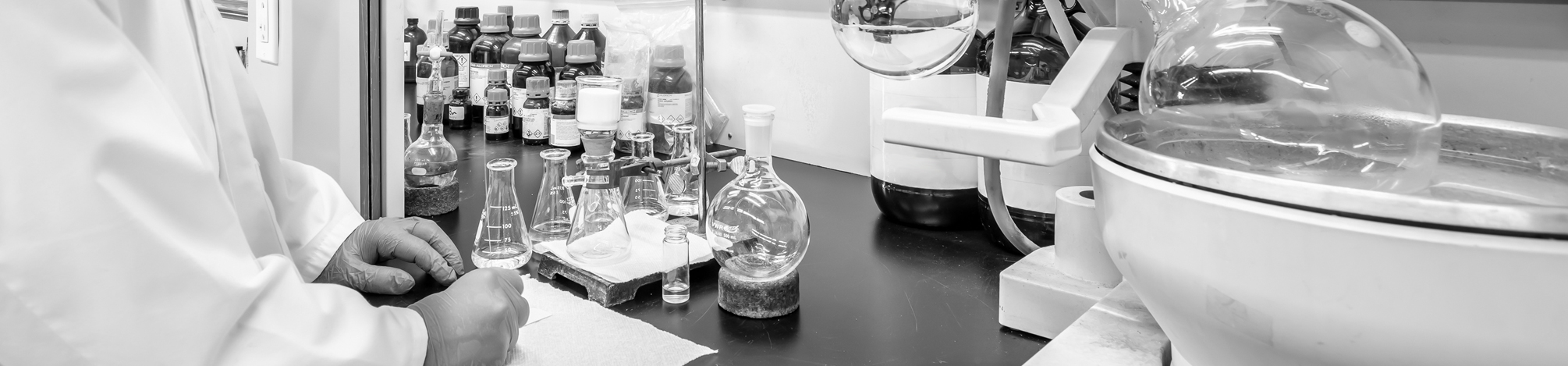 Close-up of fume hood with a rotary evaporator and a chemist conducting column chromatography.