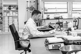 Chemist seated at bench using a laptop, fume hoods and shelves of chemicals in the background, lab equipment in the foreground.