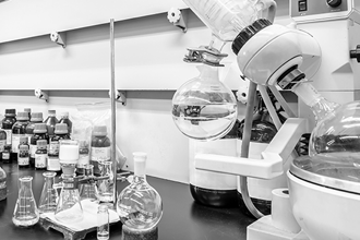 Close-up of fume hood with rotary evaporator and small Erlenmeyer flasks.
