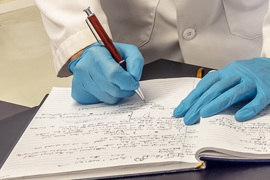 Person in a lab coat writing in a notebook.