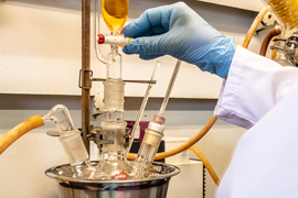 Chemist operating a valve on a reaction flask under inert gas.